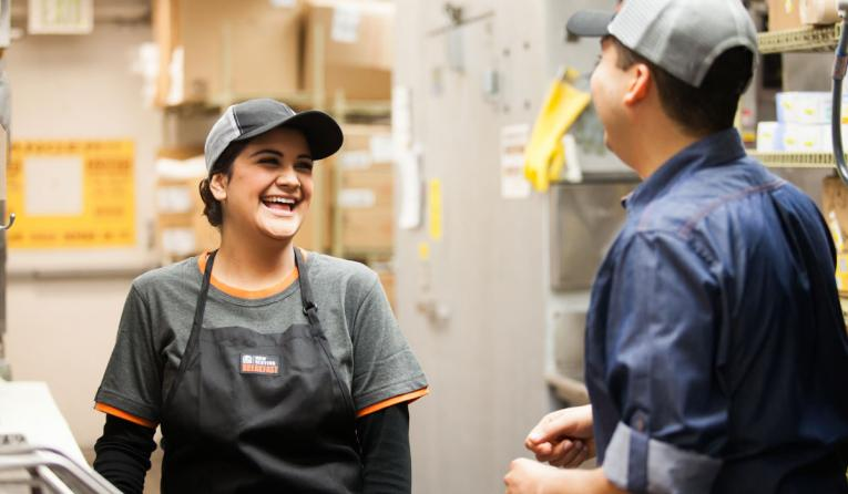 Taco Bell employees laugh in the kitchen.