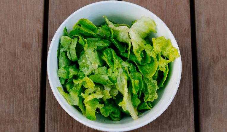A bowl of lettuce on a wood table background.
