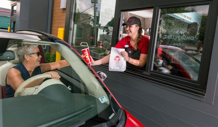 Wendy's employee serves a customer through the drive-thru lane.