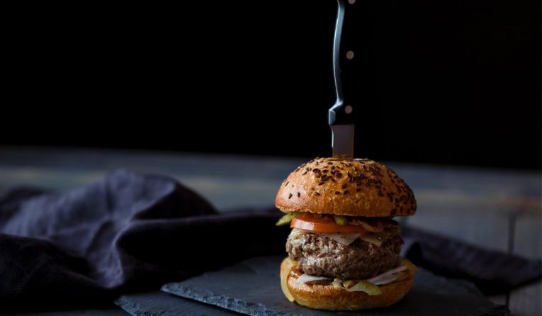 Burger skewered with knife near black textile.