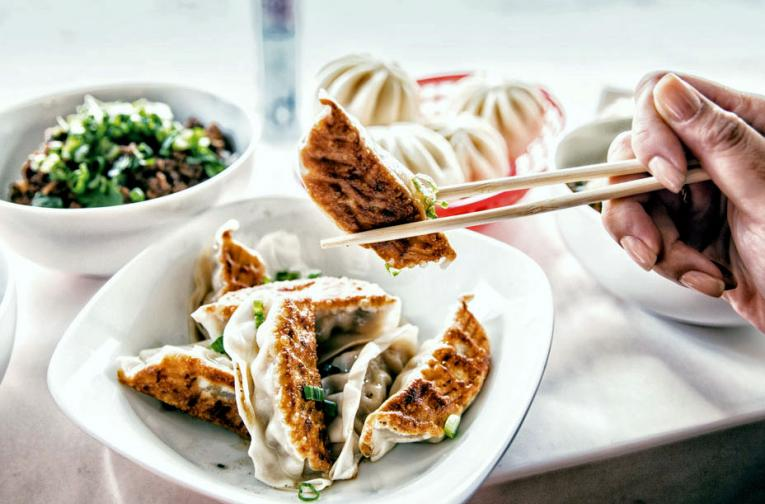 A diner eats Wow Bao dumplings with chop sticks. The fast casual is a leader in innovation.