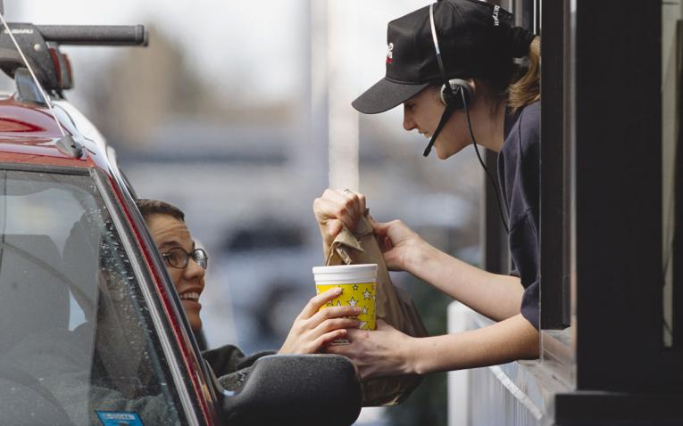 A drive-thru worker hands a customer their food.