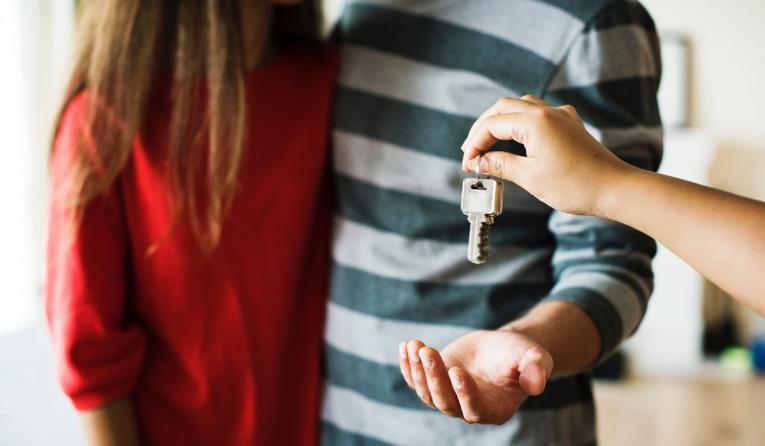 Two homeowners receive the keys to their new house.