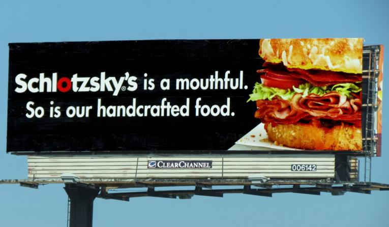 A Schlotzsky's billboard reads: Schlotzsky's is a mouthful. So is our handcrafted food.