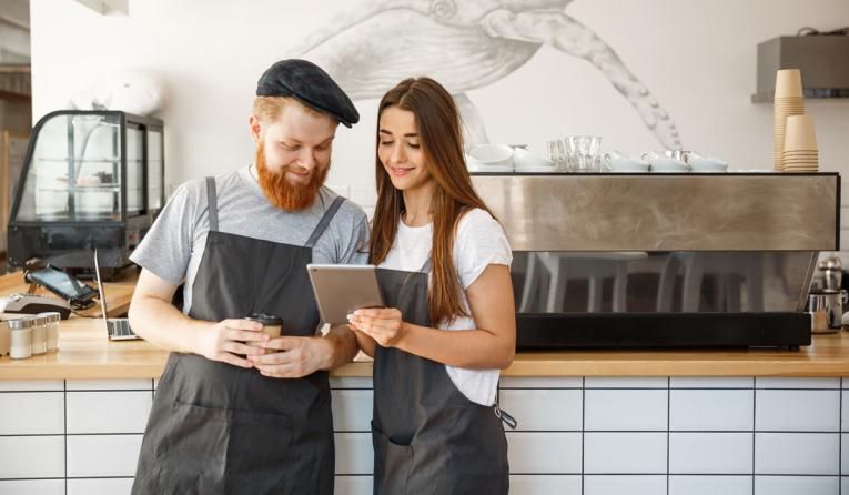 Two restaurant workers look over a tablet device.