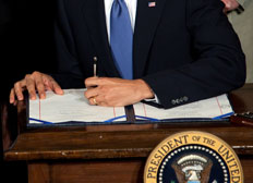 President Barack Obama signs the health insurance reform bill on March 23.