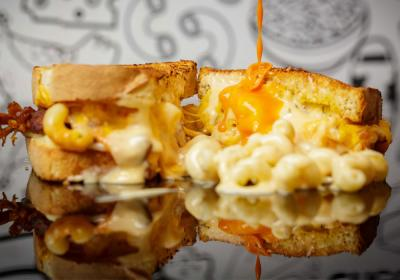 Mac & Cheese sandwich with cheese dripping over the top.