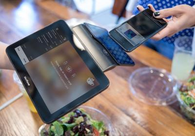 Contactless card payment between a serve and guest at a restaurant.