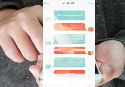 Automatic chatbot message screen with hand holding mobile phone background.