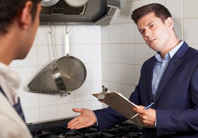 Health inspector meeting with chef In restaurant kitchen.